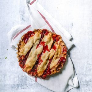 Large baked vegan strawberry and rhubarb pie.